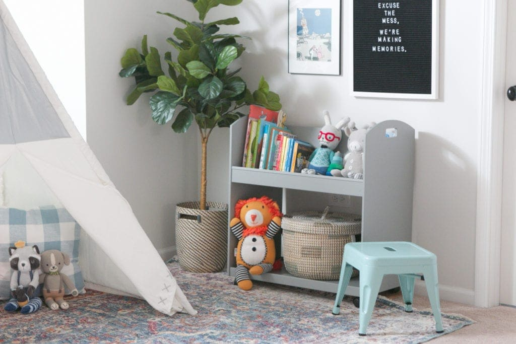 A faux fiddle leaf, bookcase on wheels, and teepee make up a play area