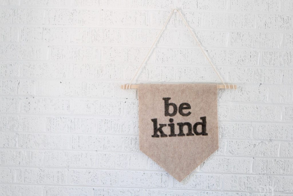 A wall pennant with the words Be Kind on it