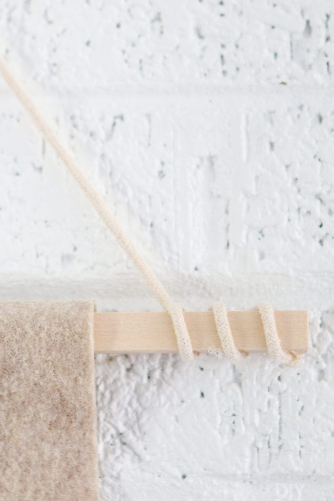 Wrap the rope around the edges of the wood dowel when making the wall pennant