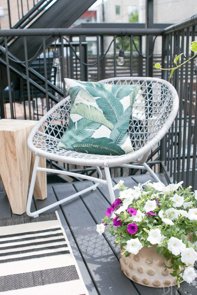 Palm print pillow on this gray outdoor lounger