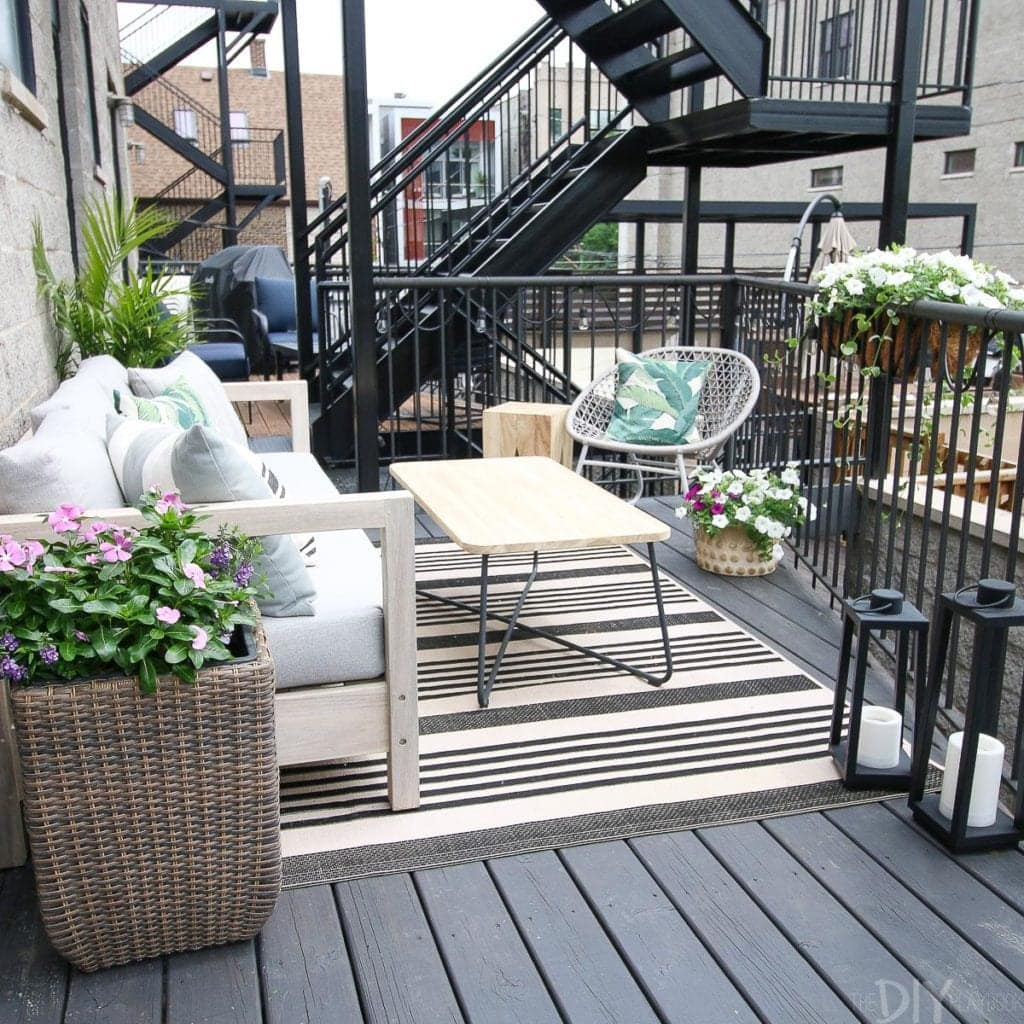 A small city patio with a couch and coffee table