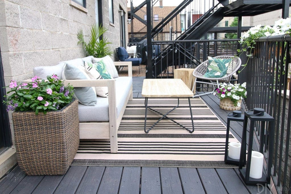 Create an outdoor room with a sofa, coffee table, and plants