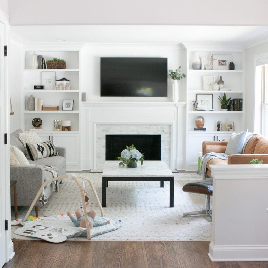 This neutral living room with a marble fireplace and white built-ins still has some work to do