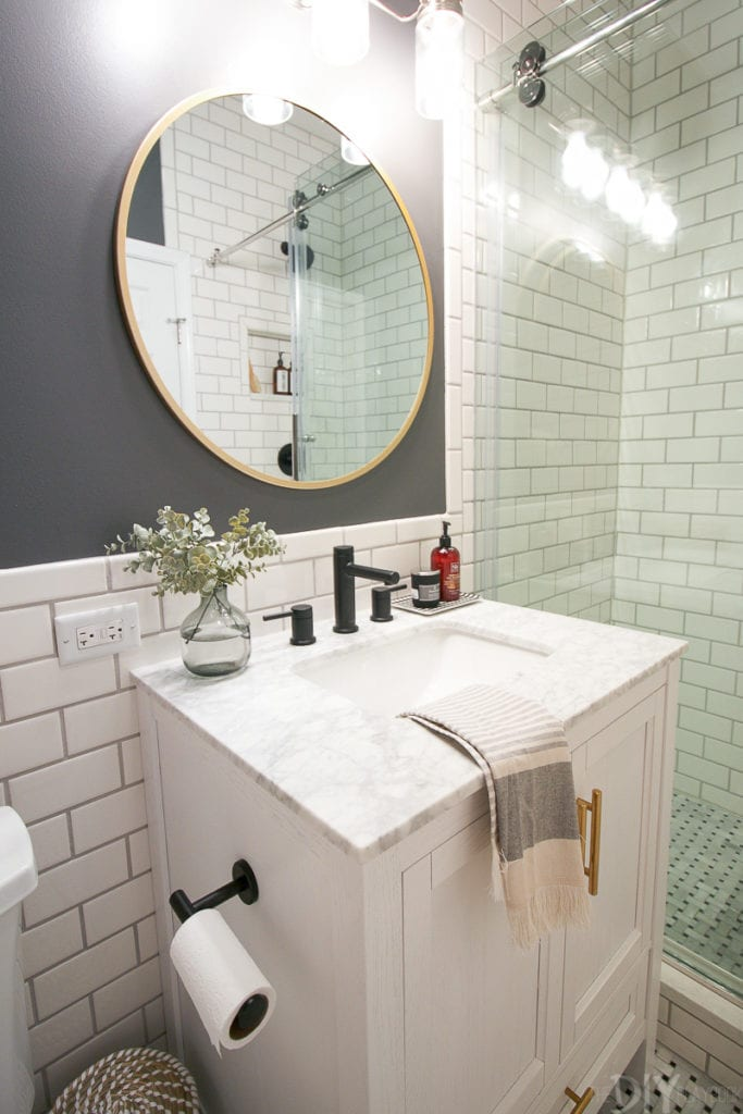 A white bathroom vanity with a gold round mirror