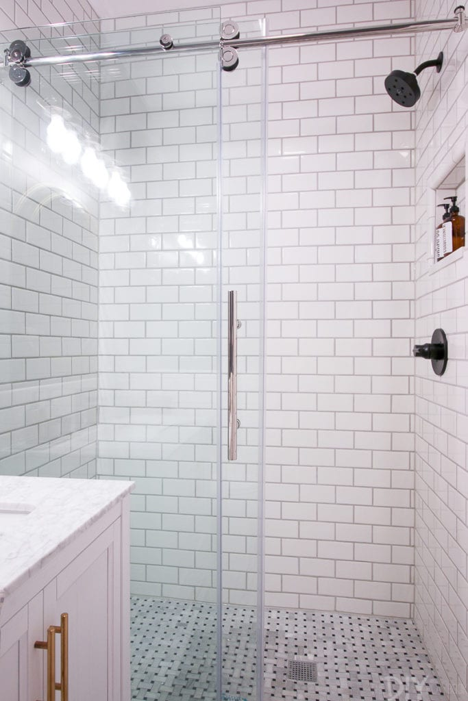 Glass shower doors show off the new subway tile in this bathroom makeover