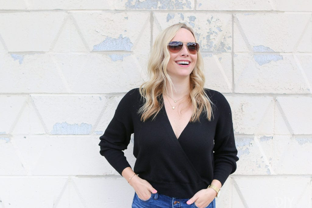 A casual black sweater with gold ray ban aviators