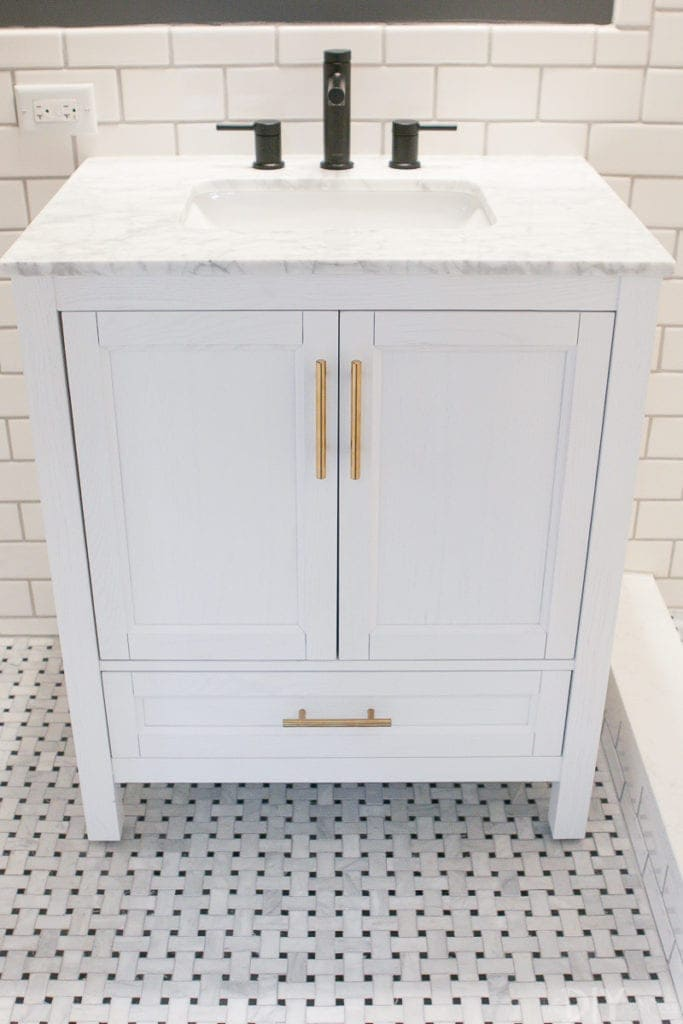 A white vanity with gold hardware and black faucet.