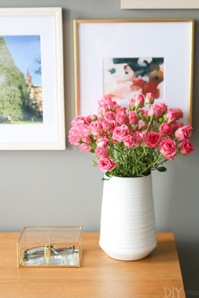 A white Homegoods vase with pink flowers