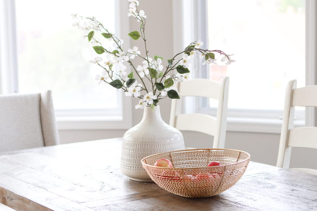 Adding branches to a white vase on a dining room table