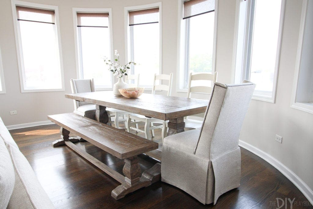 A farmhouse style wood table with wood chairs, a bench, and upholstered end chairs