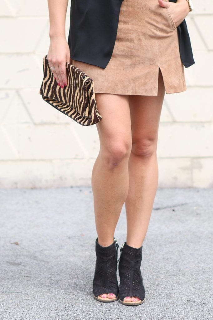 Tan suede skirt with black booties and leopard clutch