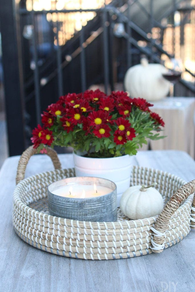 A coffee table with a tray, candle, and mini pumpkin