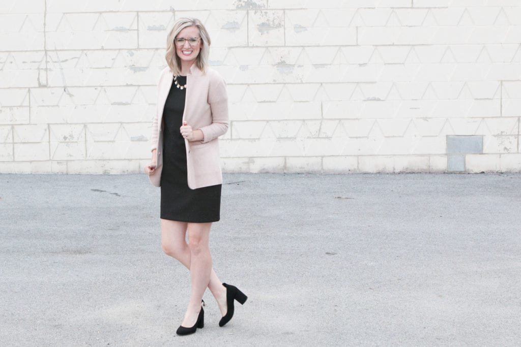 A black dress, necklace, and cream blazer