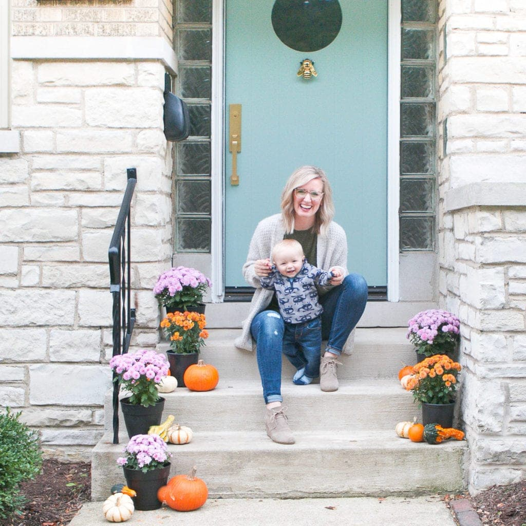 Bridget and Ben on the front porch with pumpkins and mums for fall