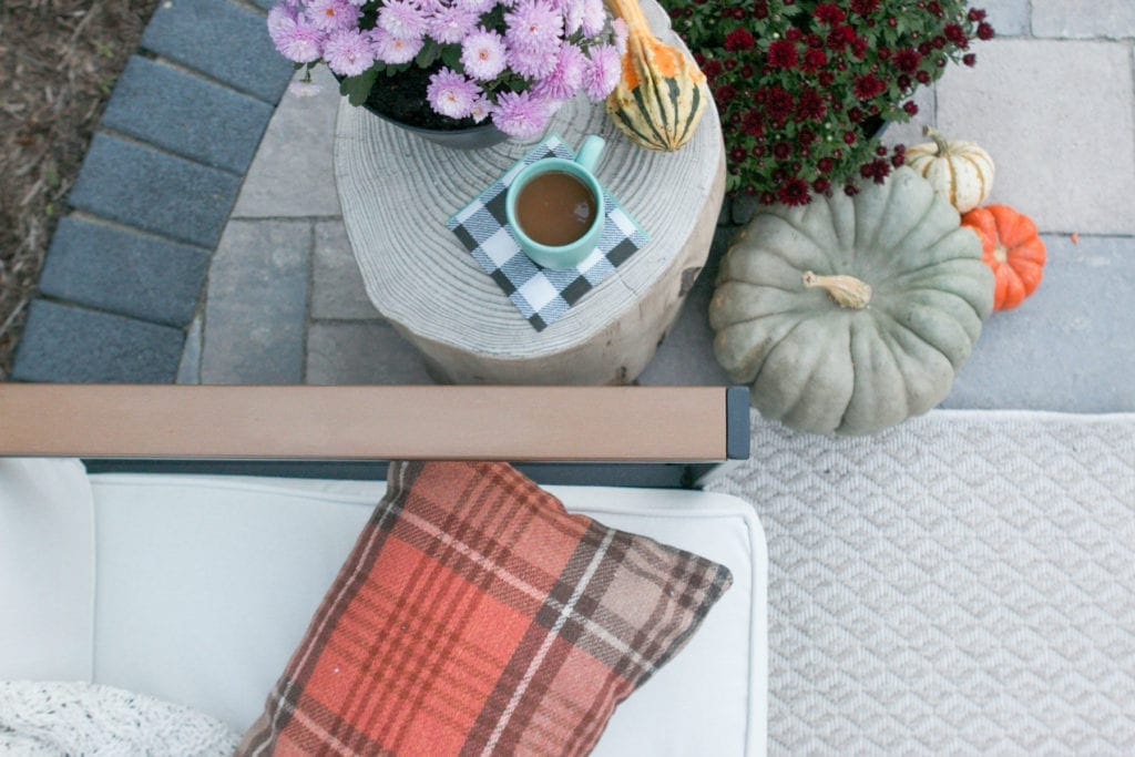 mums and pumpkins and plaid on a fall patio