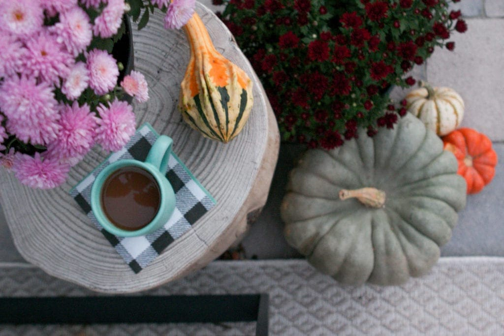 fall patio with plaid and colorful mums and pumpkins