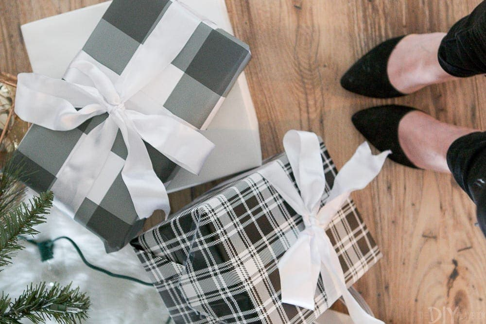 Wrapped presents under the tree with white bows and gray plaid wrapping paper.