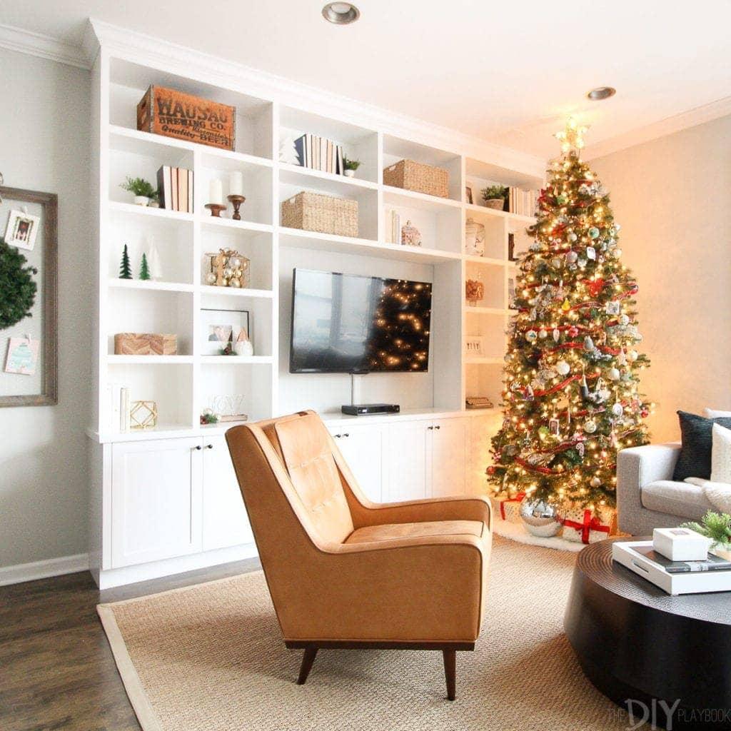 A Christmas tree near white built-ins
