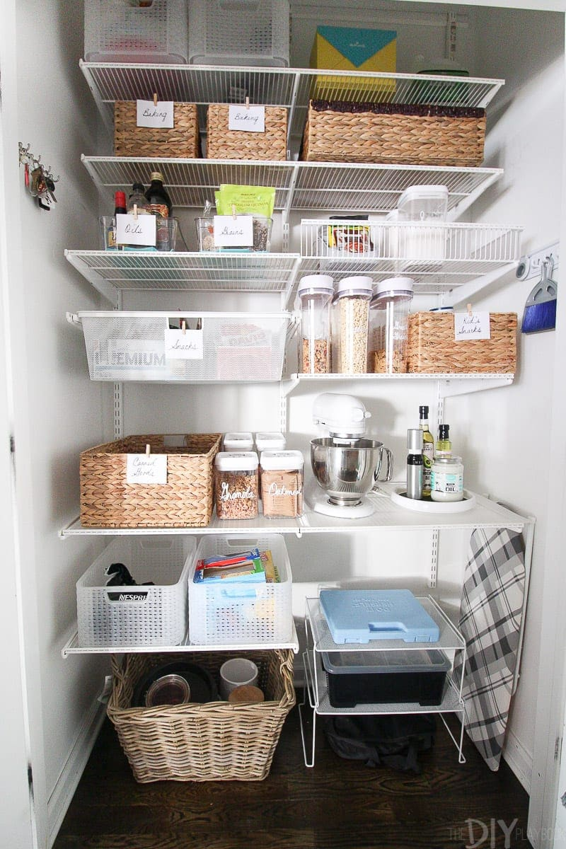 An organized pantry with labels and wicker baskets