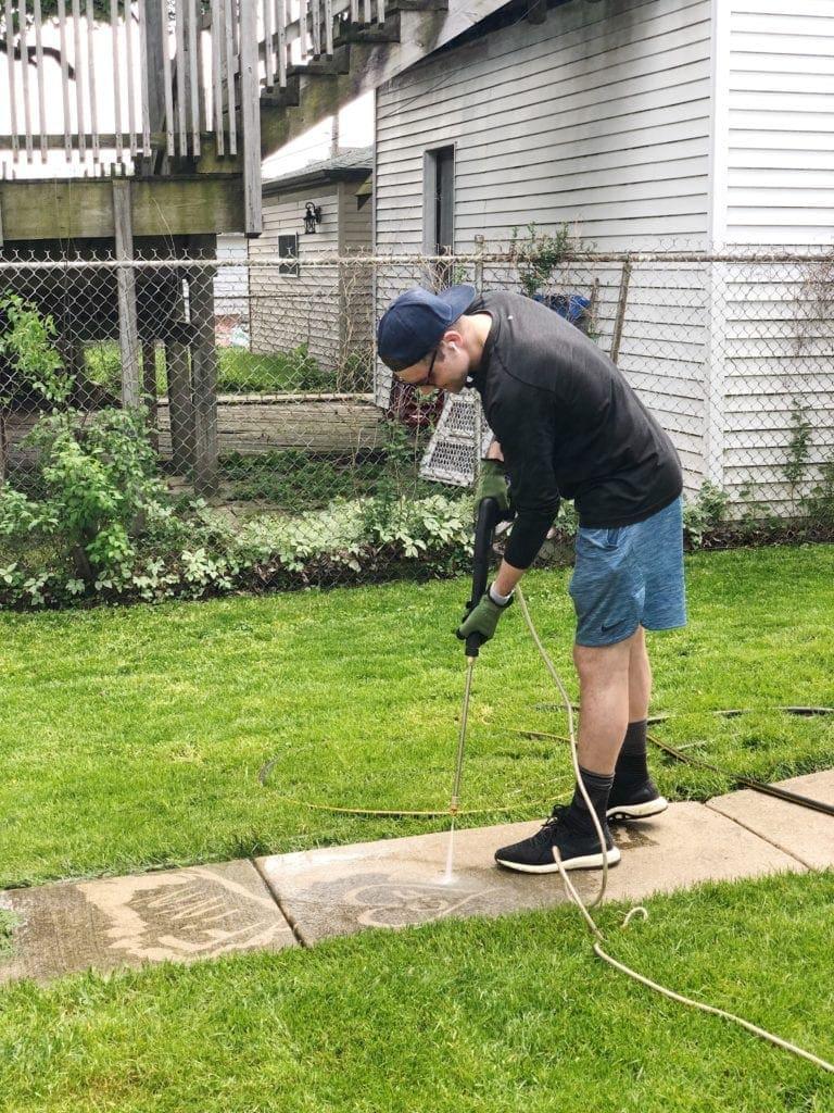 Finn power washing the sidewalk