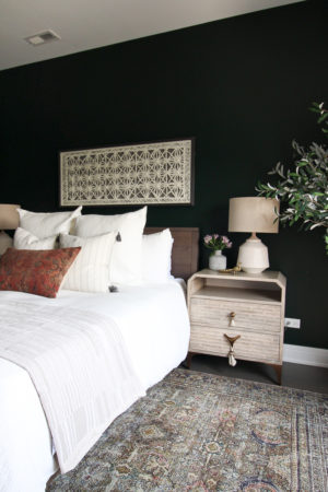 Dark green guest room with white bedding