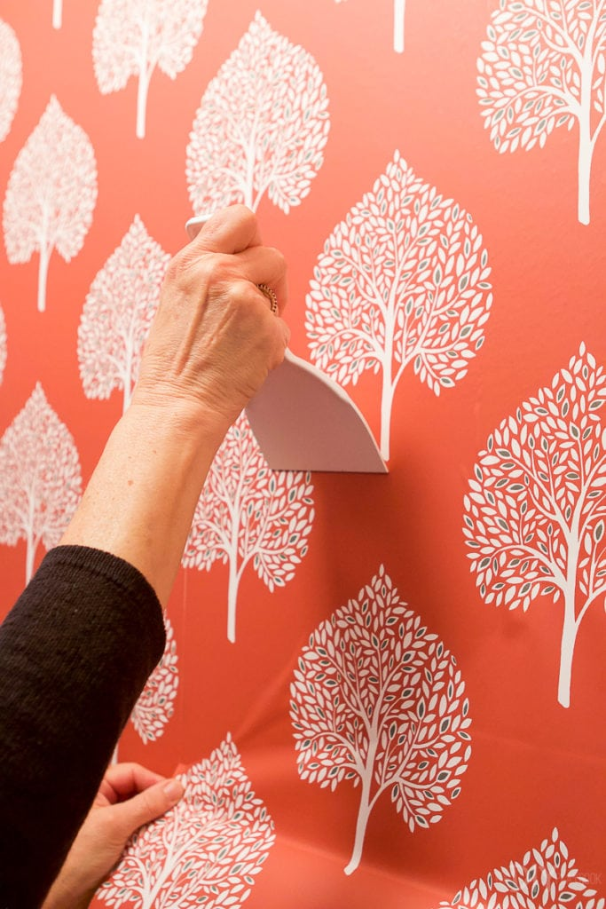 Use the plastic smoother to install your peel and stick wallpaper