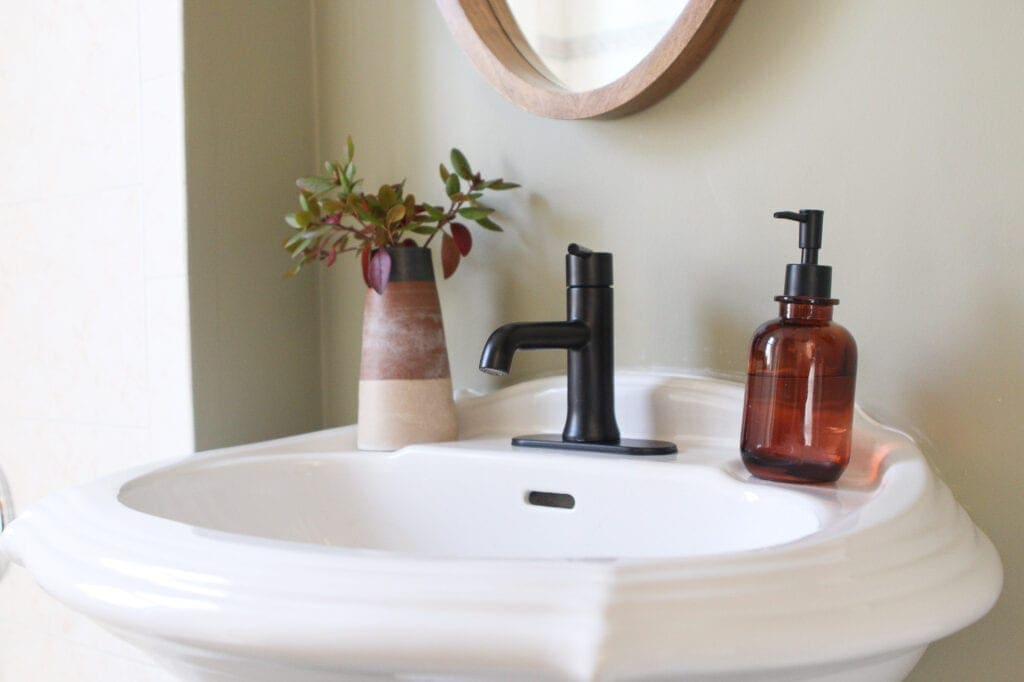 Pedestal sink and black faucet