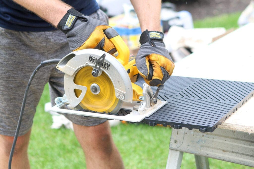 using a circular saw to cut garage floor tiles
