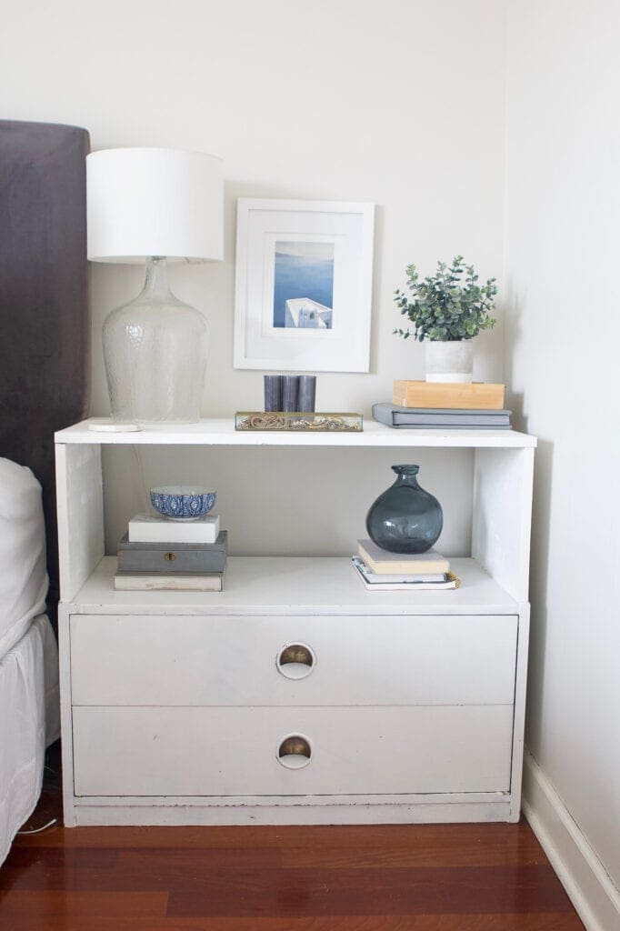 White nightstand with lamp and styling