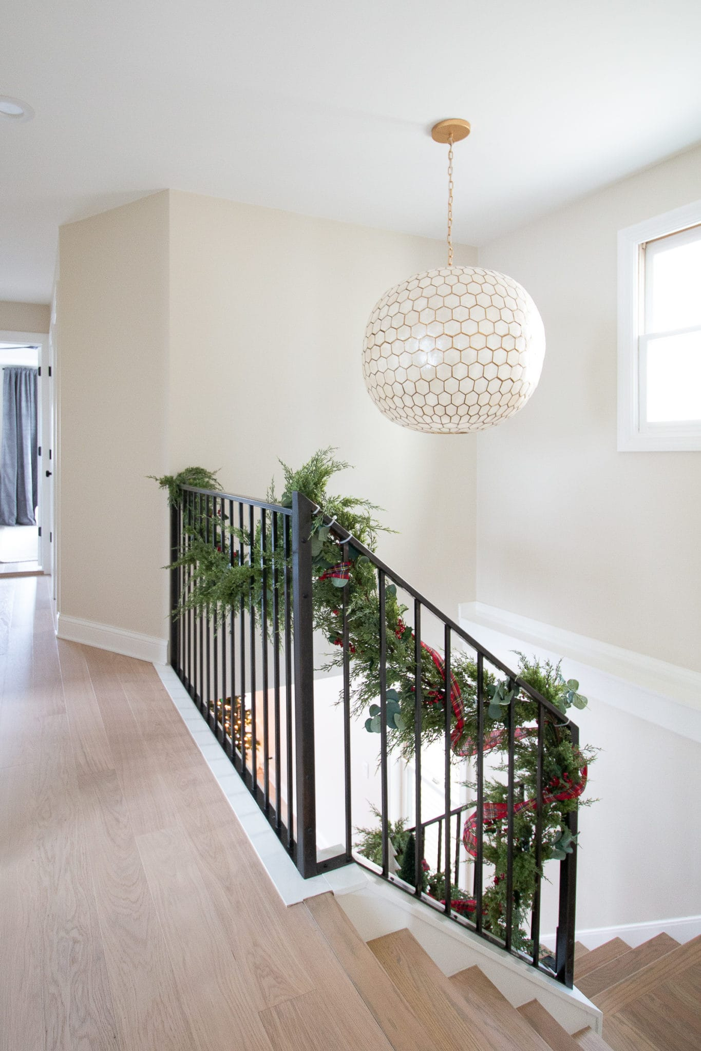 Adding garland to our staircase banister for Christmas
