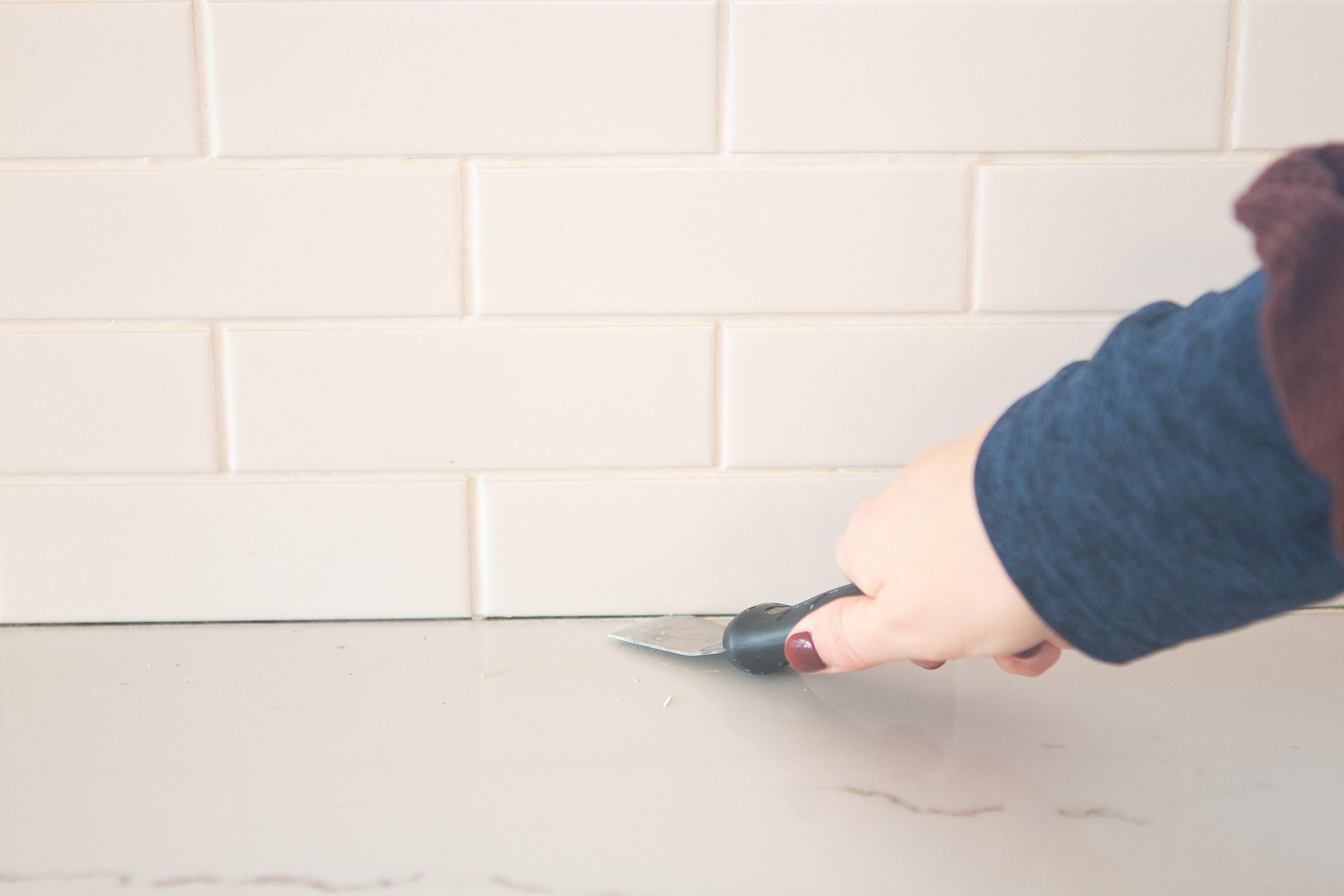 Scrape away the old grout