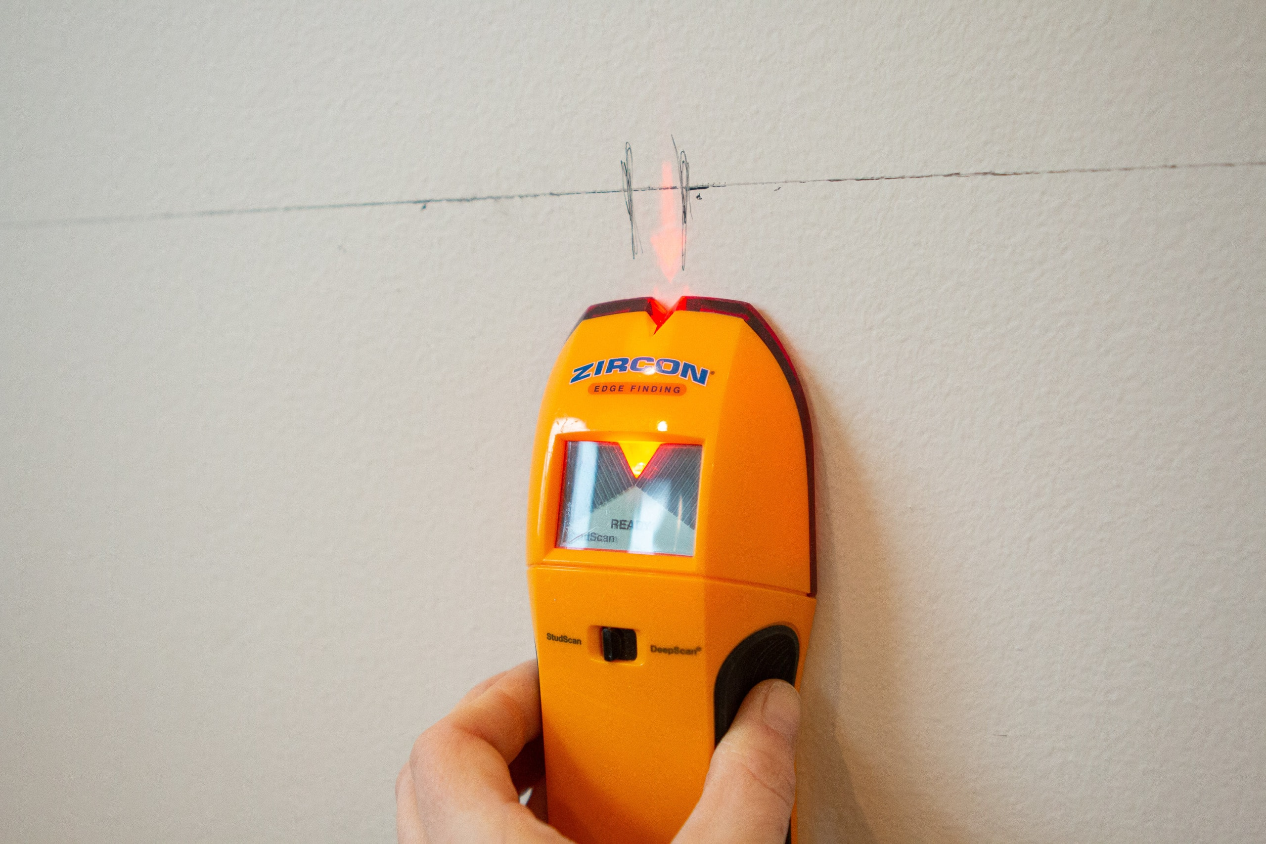 Using a stud finder to find studs