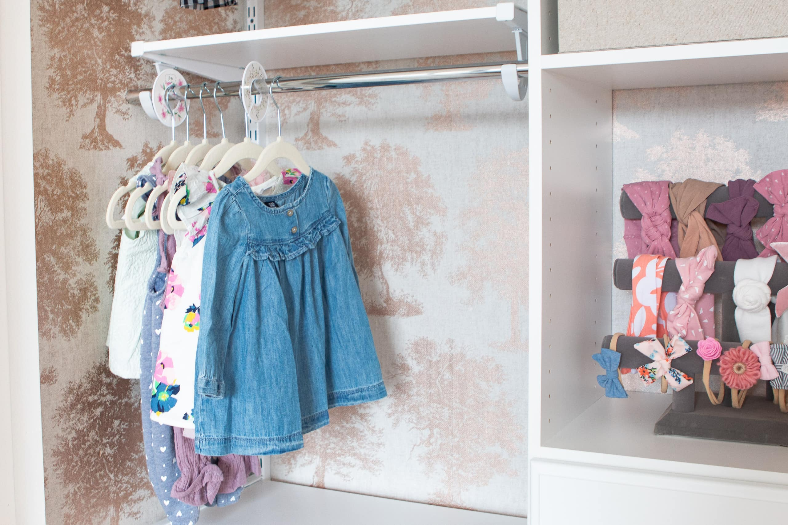 Hanging baby clothes in an organized nursery closet