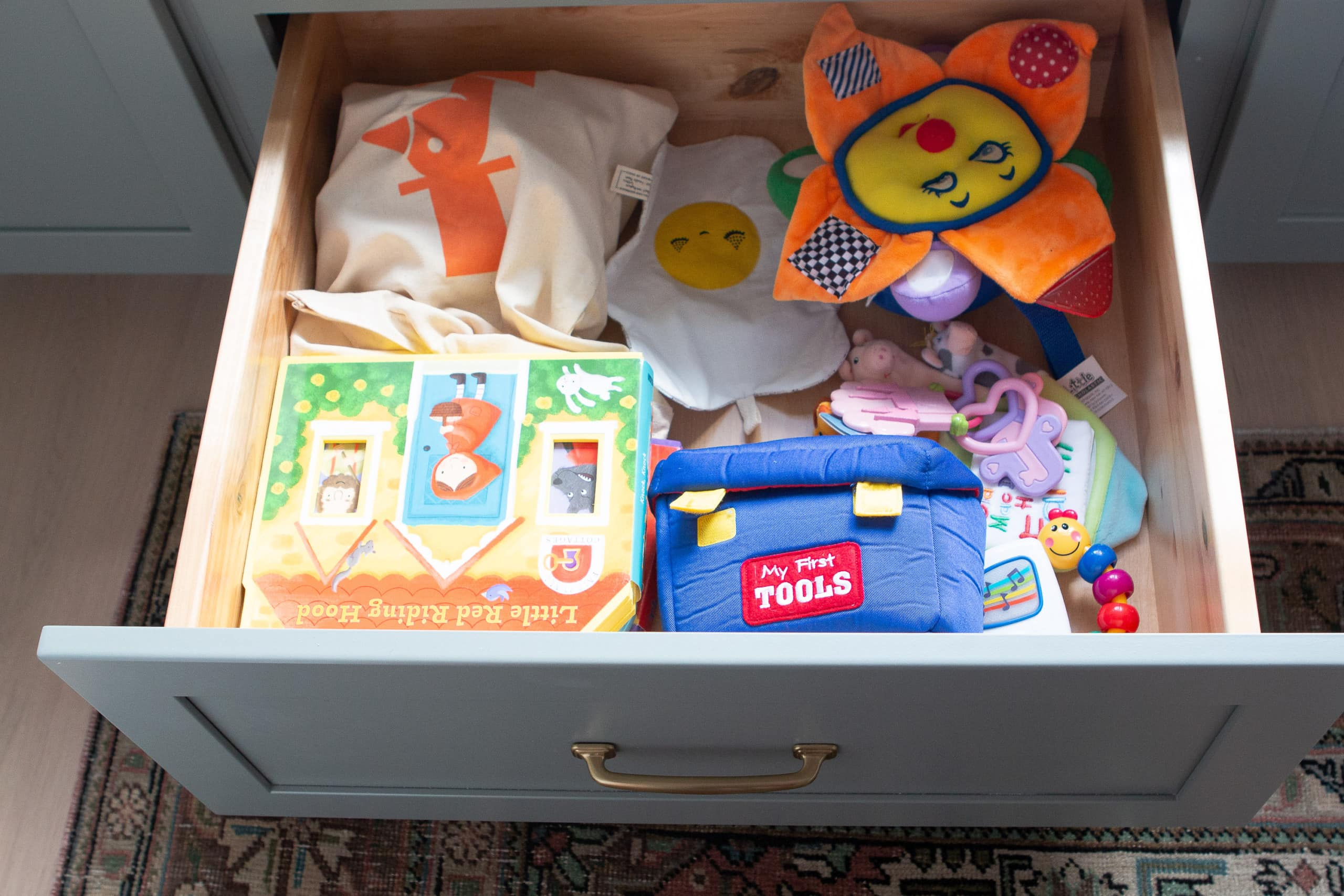 Adding toys to a drawer in the nursery