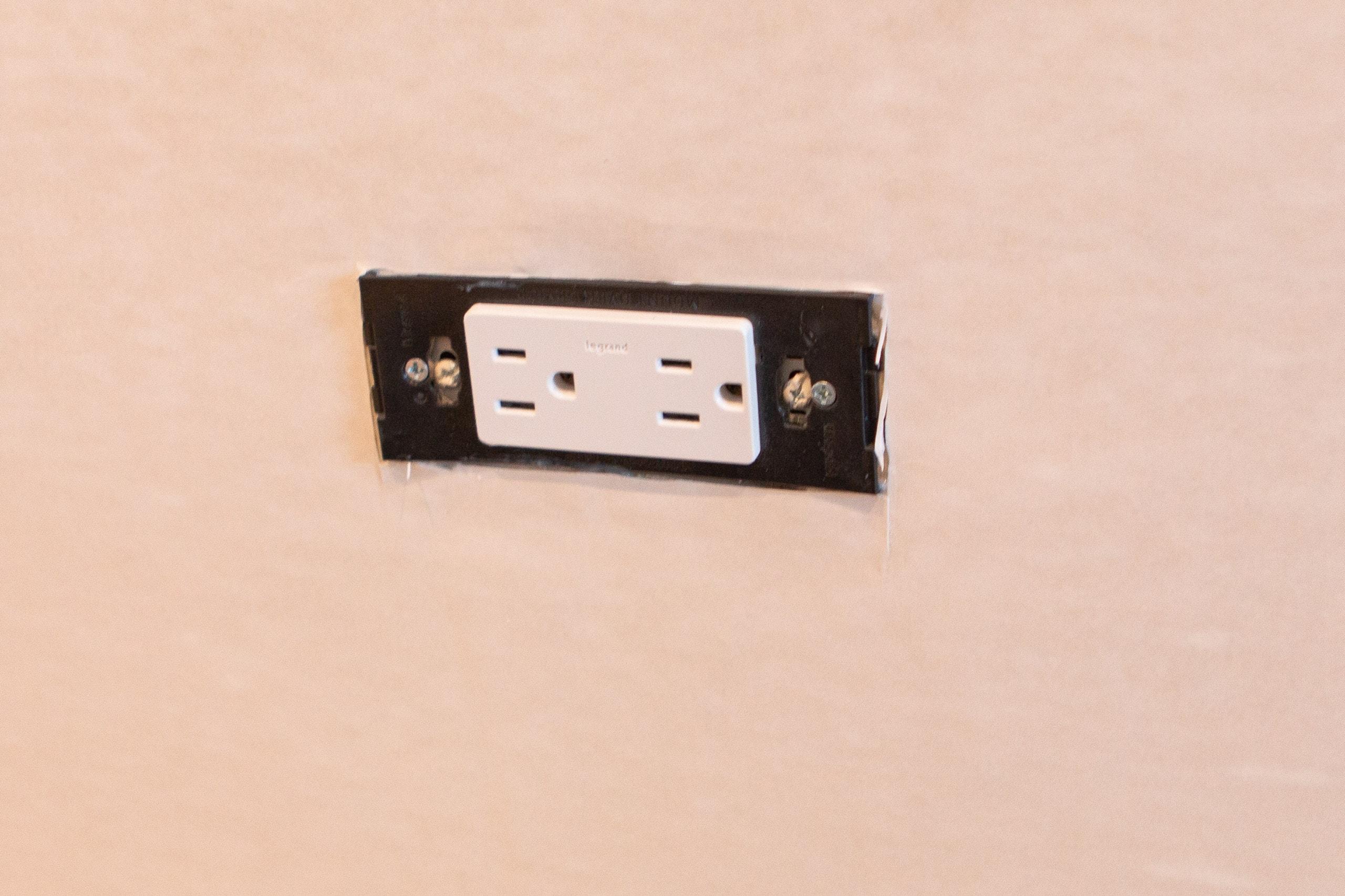 Cutting wallpaper around an outlet