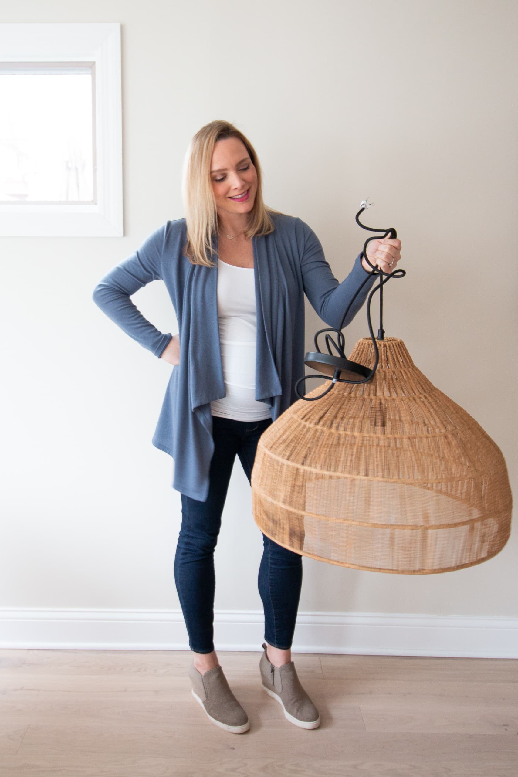 Casey holding light fixture from crate and barrel