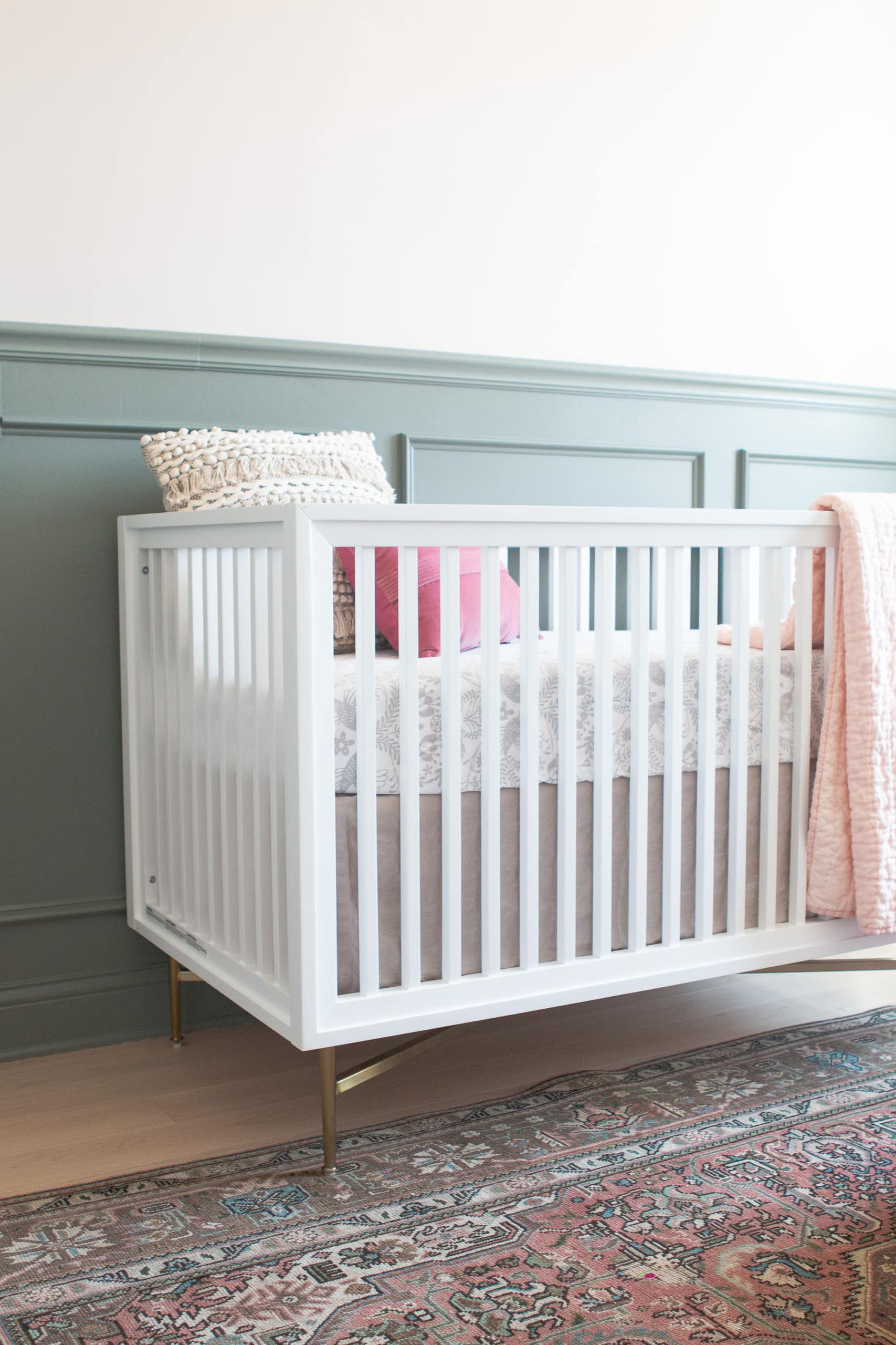 White crib against sage green chair rail