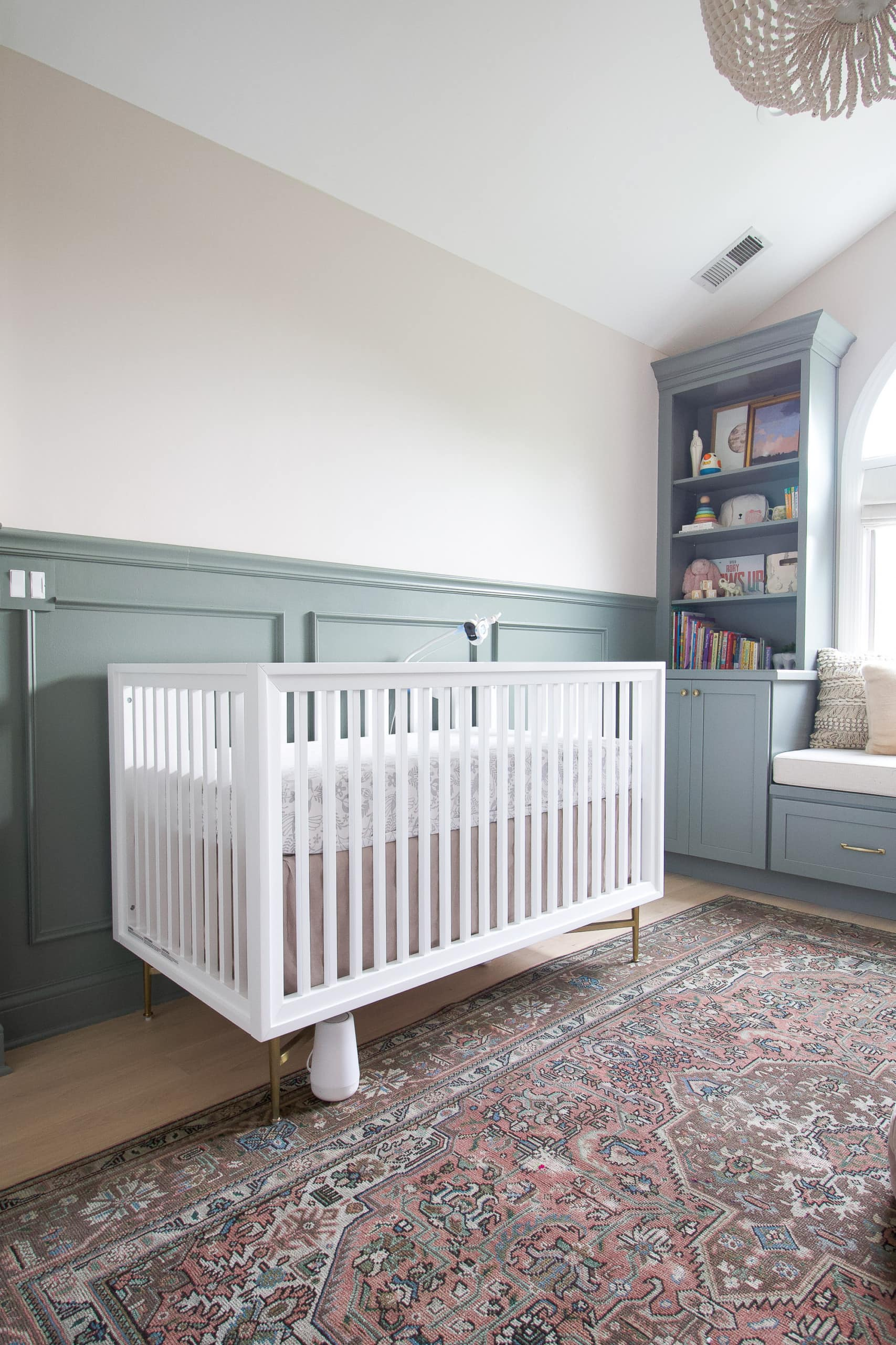 White crib in a sage and blush nursery