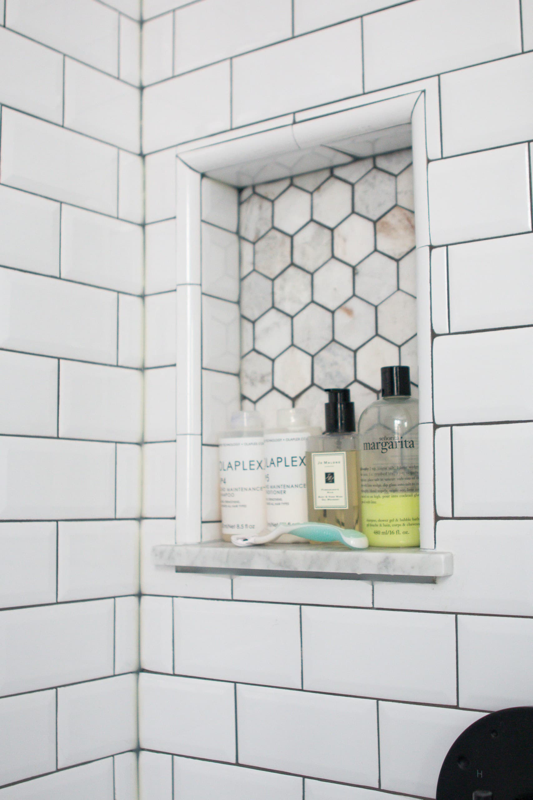 Shower niche in a marble and white bathroom
