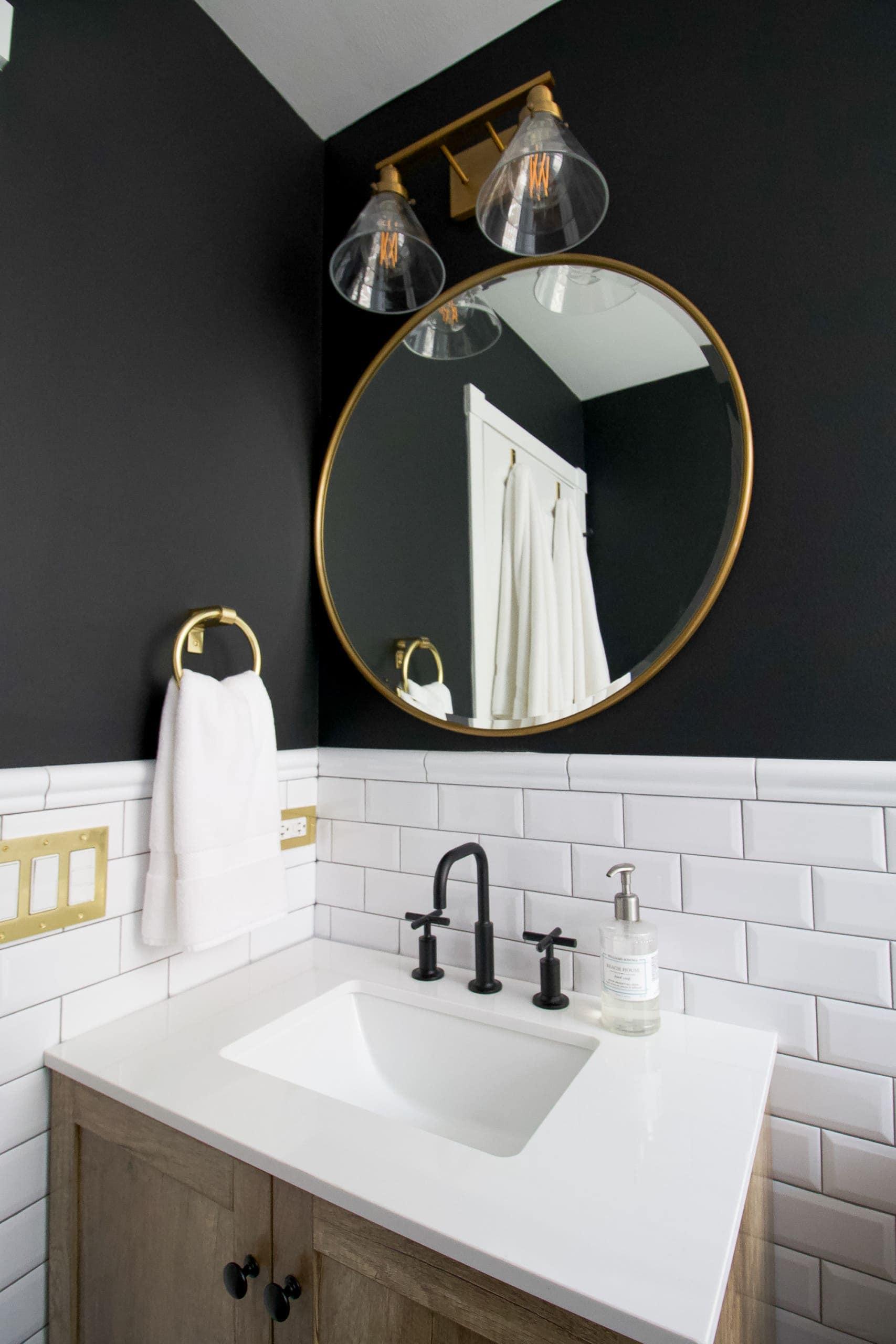 A bathroom vanity with gold mirror