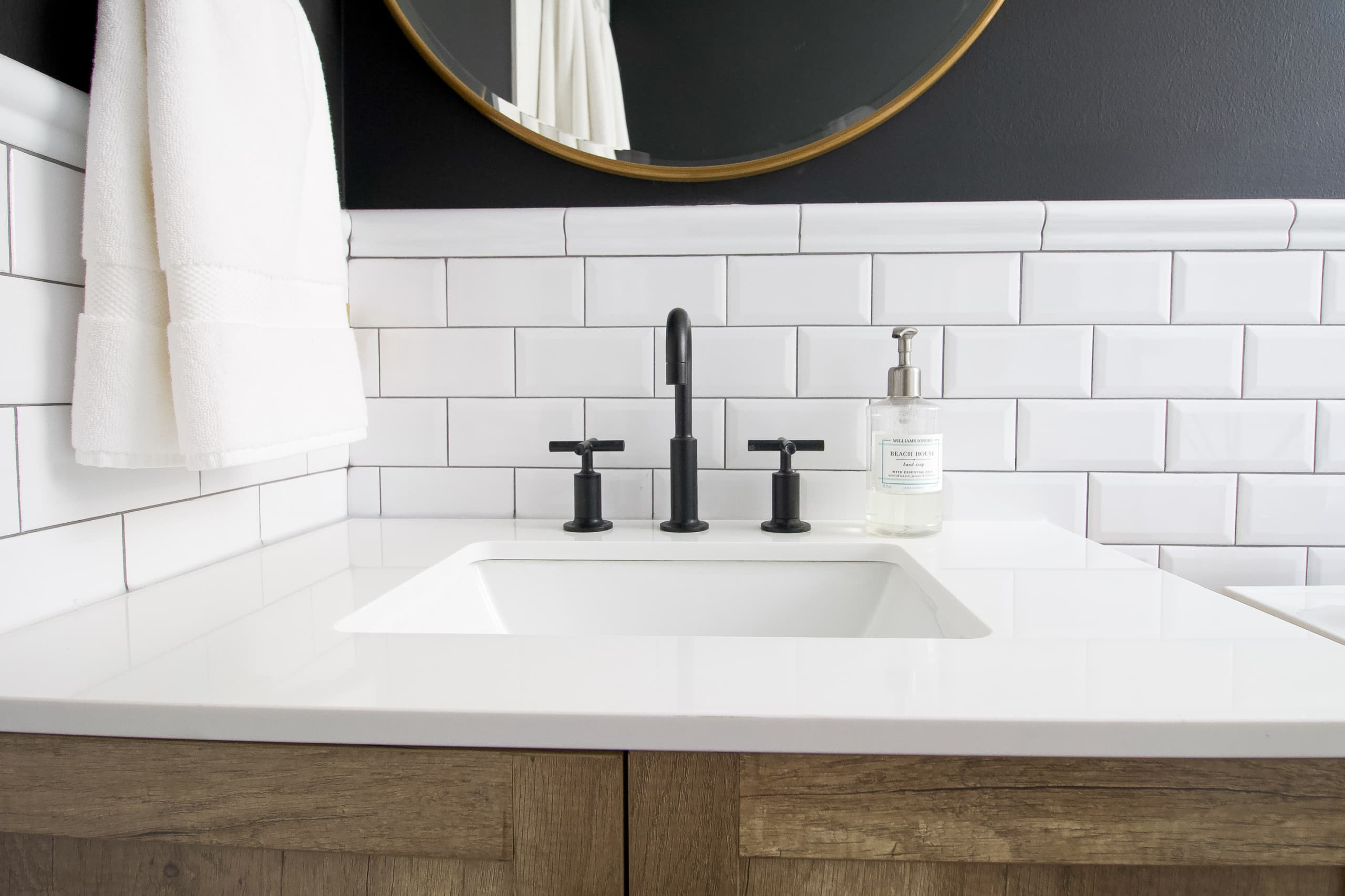 Using a black faucet in this black and white bathroom remodel